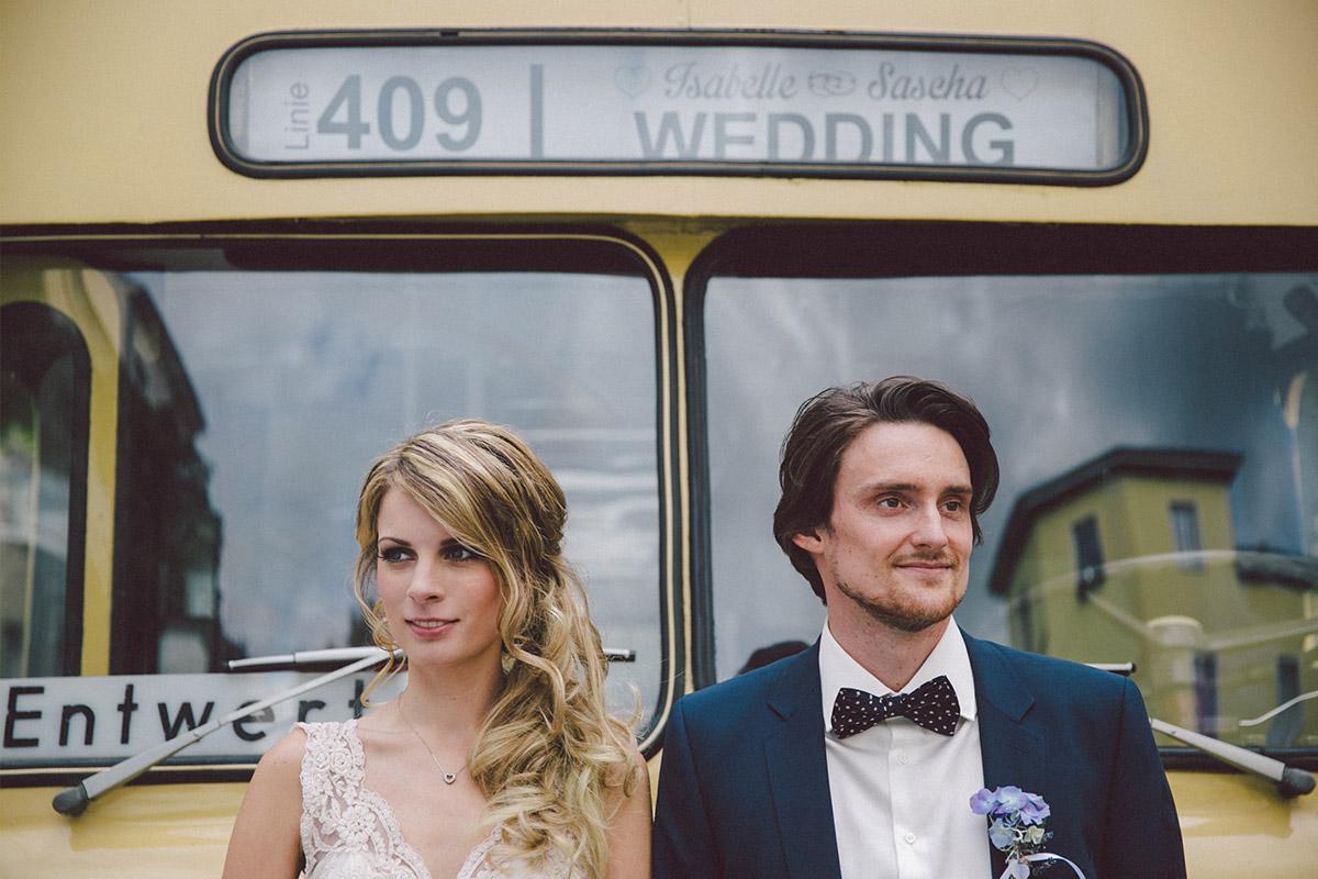 Brautpaarfoto vor vintage BVG-Bus bei Vintage-Hochzeit im Ballsaal-Studio Berlin © Hochzeitsfotograf Berlin www.hochzeitslicht.de