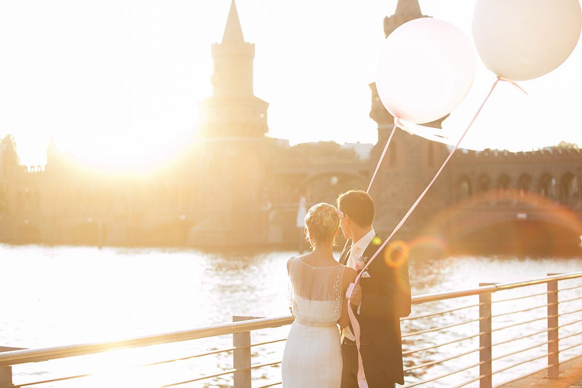 Hochzeitsfotografie von Brautpaar bei Sonnenuntergang mit Riesenluftballons an Oberbaumbrücke © Hochzeitsfotograf Berlin www.hochzeitslicht.de