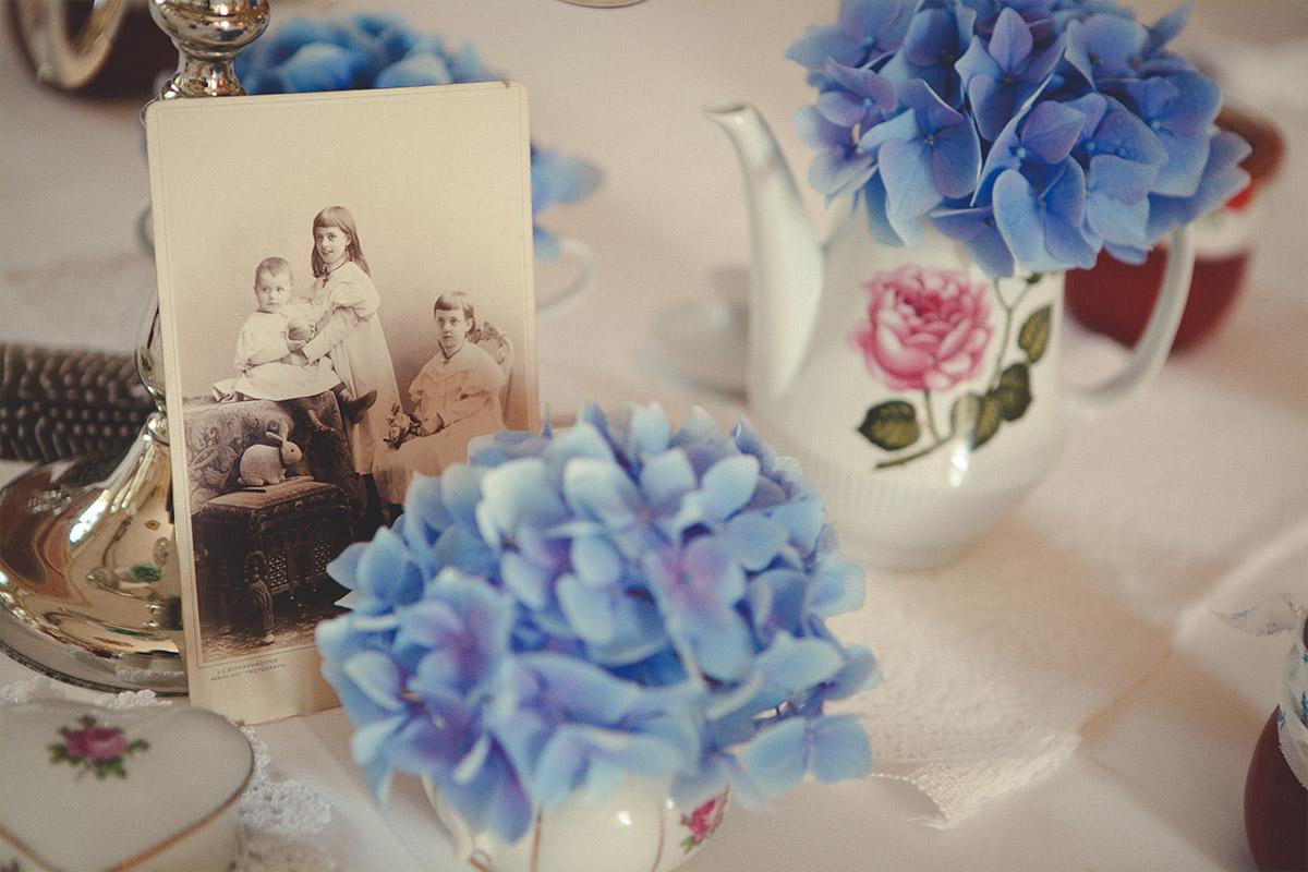 Tischdekoration im Vintage-Stil mit Hortensien, alten Fotografien und traditionellem Porzellan bei Schloss Marquardt Hochzeit © Hochzeitsfotograf Berlin hochzeitslicht