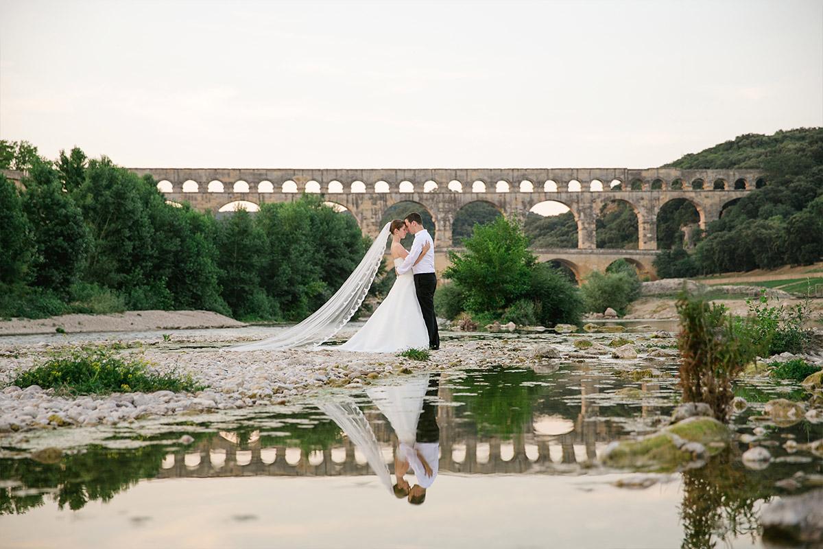 Hochzeitsfotografie von Brautpaar vor Aquädukt in der Provence, Frankreich und Reflektion des Brautpaares im Wasser © Hochzeitsfotograf Berlin hochzeitslicht