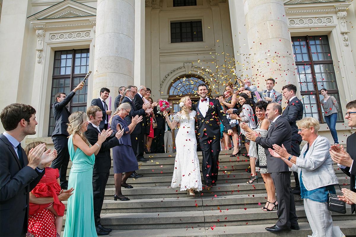 Hochzeitsreportagefoto von Brautpaar im Konfettiregen aus Konfettikanonen nach freier Trauung im Französischen Dom, Berlin © Hochzeit Berlin www.hochzeitslicht.de