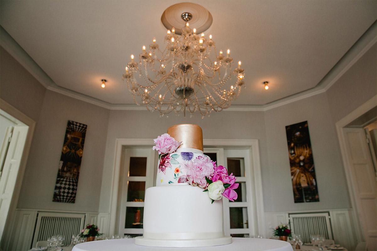 Dreistöckige Hochzeitstorte mit Dekor in Kupfer und buntem Blumendekor bei Hochzeit im Gästehaus Villa Blumenfisch © Hochzeitsfotograf Berlin www.hochzeitslicht.de