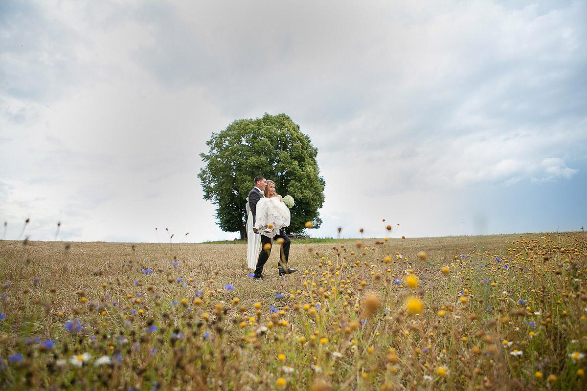 Hochzeitsfoto von Brautpaar in Feld aufgenommen in der Nähe von Schloss und Gut Liebenberg © Hochzeitsfotograf Berlin hochzeitslicht