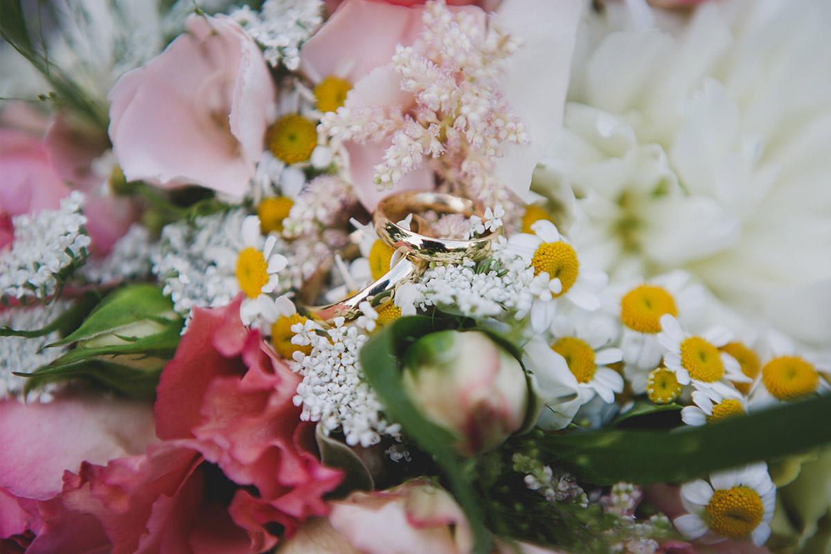 Detailfoto der Eheringe auf Brautstrauß aus pinken und weißen Blumen bei Sommerhochzeit im Schloss Marquardt Potsdam © Hochzeitsfotograf Berlin www.hochzeitslicht.de