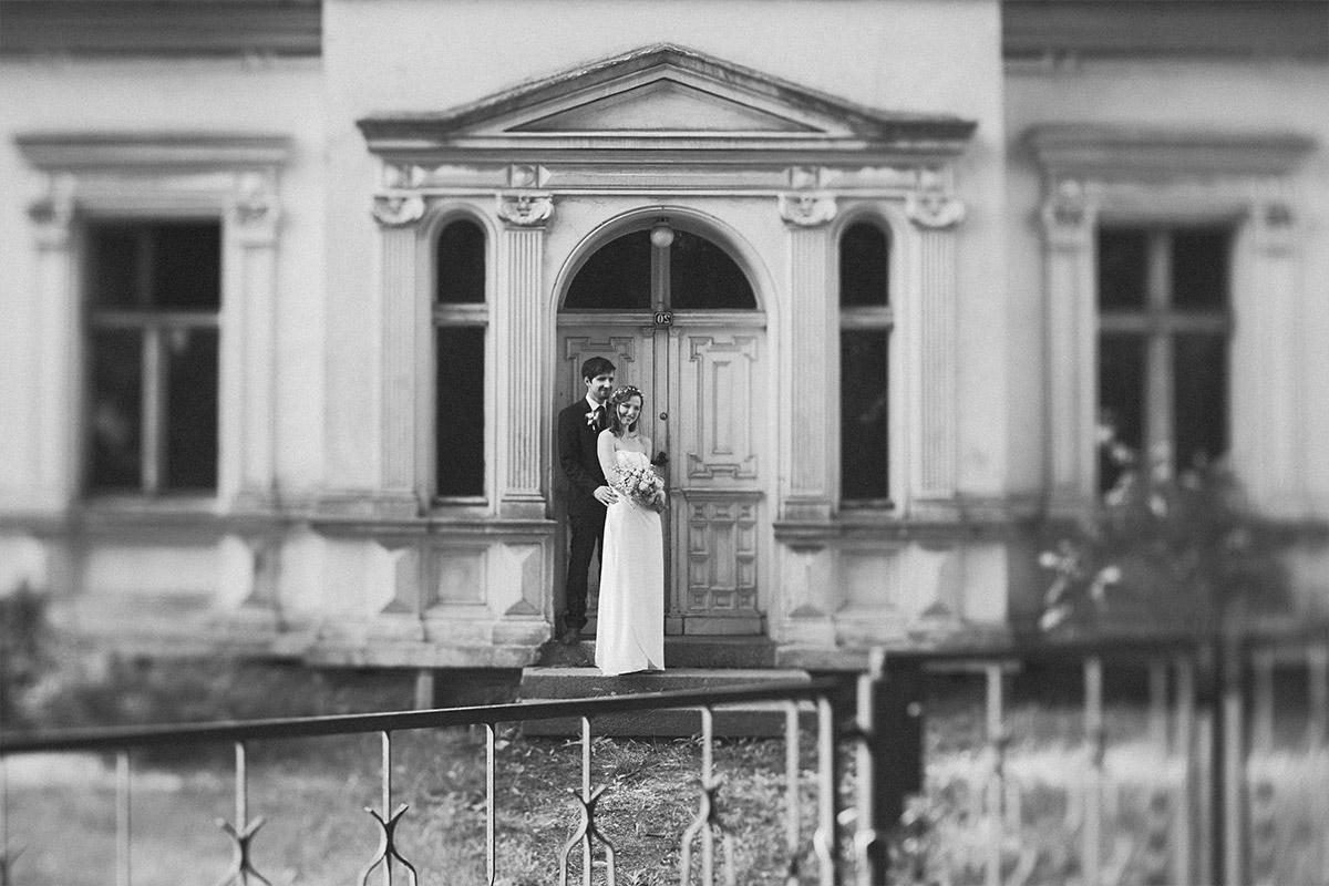 Schwarz-Weiß Hochzeitsfoto von Braut und Bräutigam vor Villa bei Spreewald-Hochzeit aufgenommen von professioneller Hochzeitsfotografin © Hochzeit Berlin www.hochzeitslicht.de