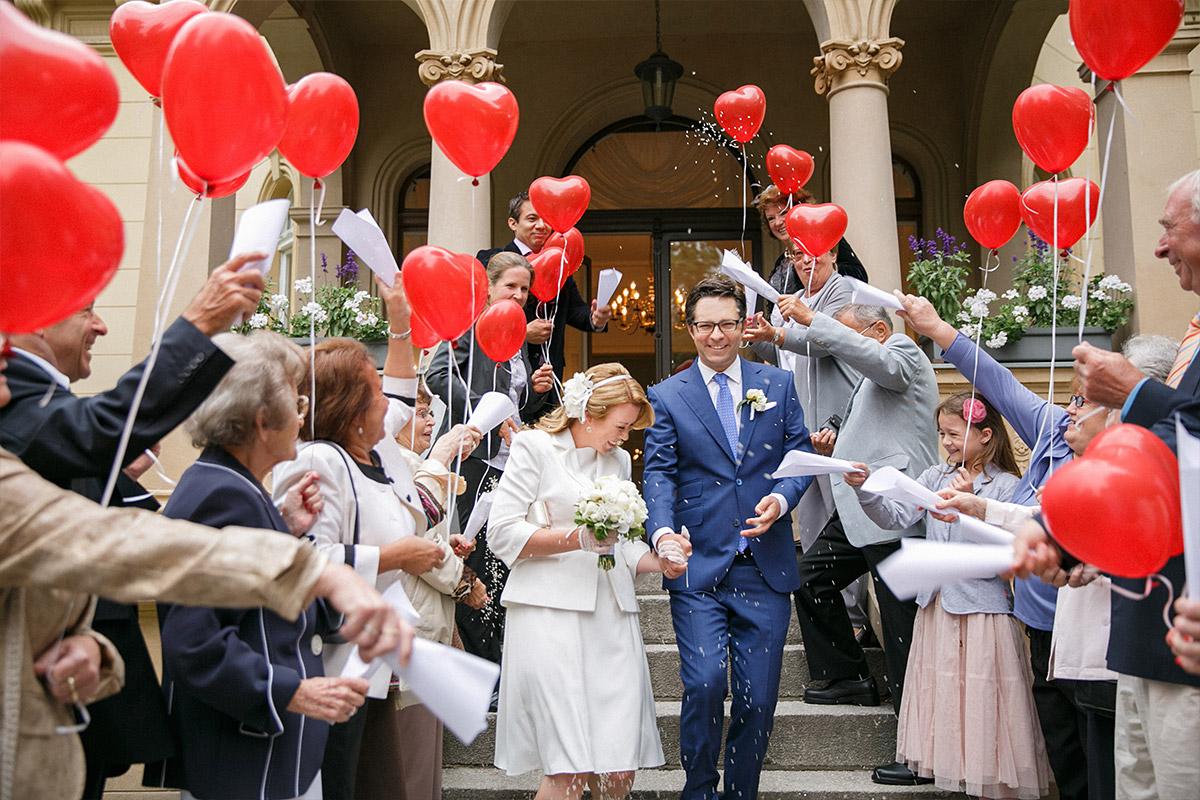 Hochzeitsreportage-Foto von Brautpaar und Gästen mit roten Herzluftballons beim Auszug nach standesamtlicher Trauung in der Hochzeitsvilla des Standesamts Steglitz-Zehlendorf © Hochzeitsfotograf Berlin hochzeitslicht