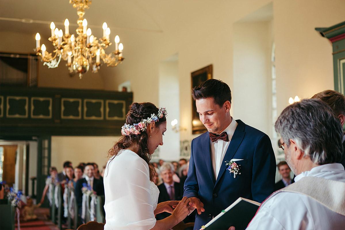 Hochzeitsfoto von Ringtausch bei Trauung in Feldsteinkirche Wulkow während Haus Tornow am See Hochzeit © Hochzeitsfotograf Berlin www.hochzeitslicht.de