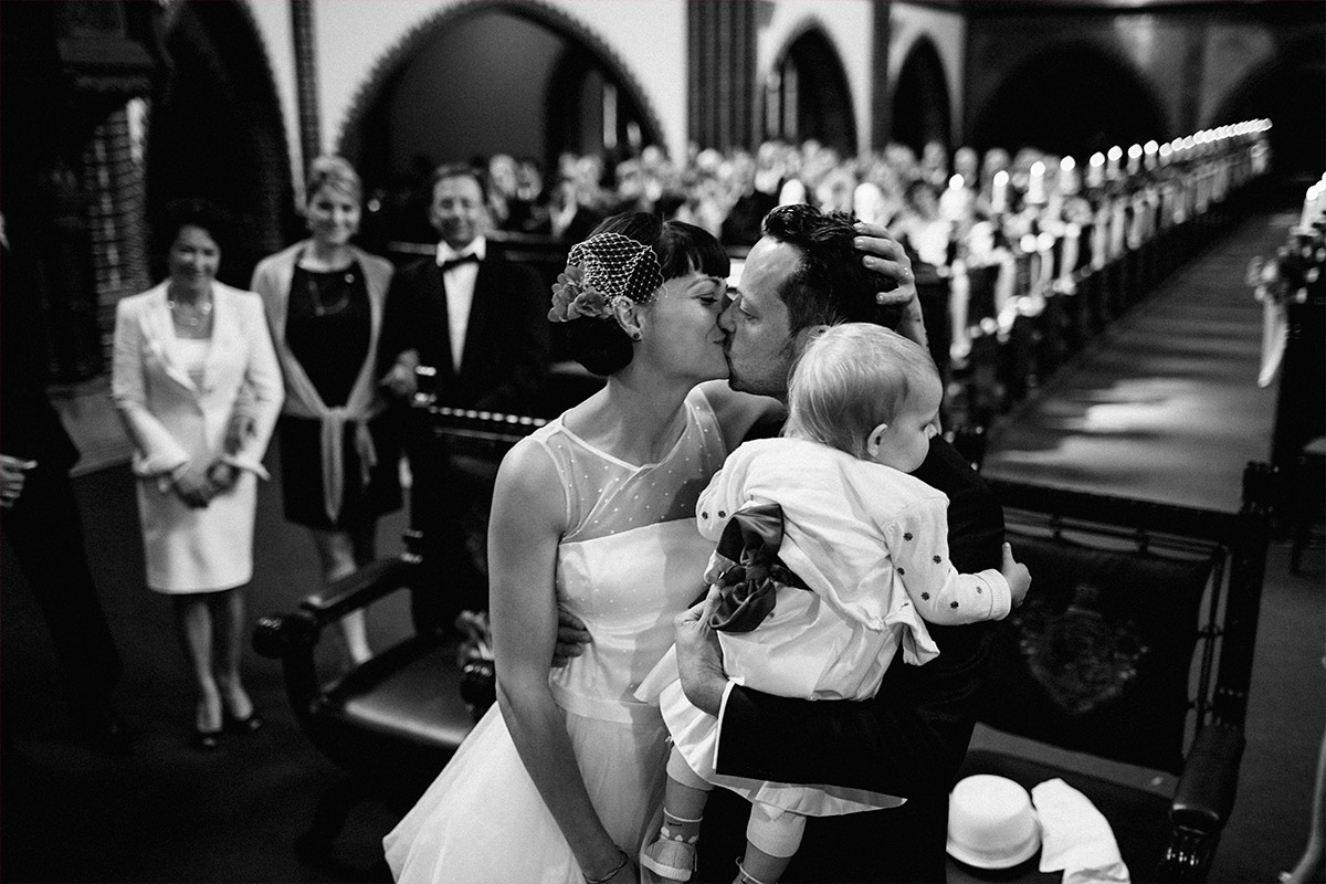 Hochzeitsfoto von Brautpaar mit Baby aufgenommen von Hochzeitsfotograf in Erlöserkirche Berlin Rummelsburg © Hochzeit Berlin www.hochzeitslicht.de