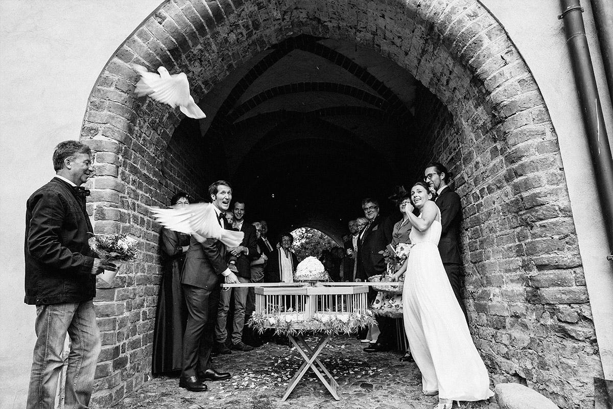 Hochzeitsreportagefoto beim Fliegenlassen von weißen Tauben aufgenommen von Hochzeitsfotograf auf Schloss Neuhausen Prignitz © Hochzeitsfotograf Berlin www.hochzeitslicht.de